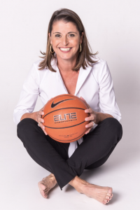 Image of Joanne P. McCallie sitting on floor holding basketball