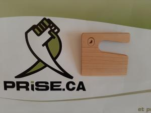 Image of the Prise, Inc., company logo next to an image of the Little Kitchen Academy child safe knife made of wood with the Little Kitchen Academy bird signet/logo in black