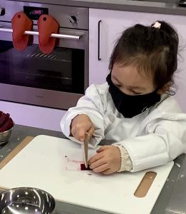 Image of a Little Kitchen Academy student (young Asian girl age 4) wearing a white chef coat cutting with the Little Kitchen Academy Child Safe Knife made of wood