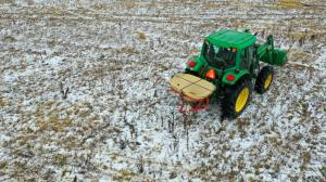 """alt=""""Green tractor on snowy field spreads native seed mix containing seeds sourced from southern Illinois and Kentucky."""""""