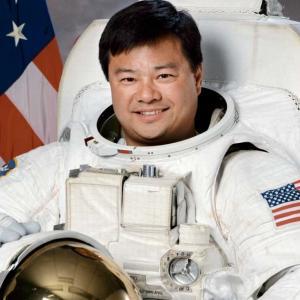 Official Astronaut Portrait of Astronaut Leroy Chiao, Ph.D., in white EVA Suit holding helmet
