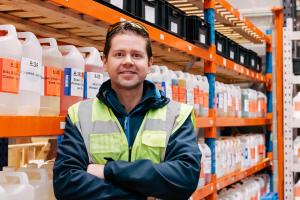 Dr Adam Hunniford of PiP Chemicals in Newtownards, Northern Ireland, UK. Adam is standing in his warehouse beside a shelving unit of chemicals.