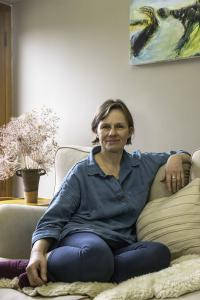 Claudi Williams looking straight at the camera whilst casually sitting on a cream coloured sofa in her home in Stroud, UK, with one arm resting on the back of the sofa, wearing denim blouse and jeans with pink ankle socks