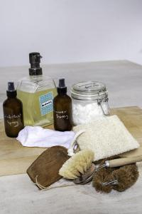 Photo shows 2 storage containers, 2 pipetter jars, a scrubbing brush and some cloths on a wooden table top