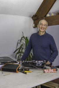 Paul Hofman wearing a dark blue shirt and jumper stands behind a table on which are tools, 2 pencils and some broken clocks