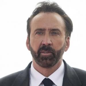 Color Photo of Nicholas Cage with beard, dressed in suit.