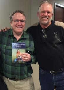 Jim Dultmeier (right) presents a book about his family's grief journey to Dr. James Hamilton, the surgeon who tried to save Jim's daughter's life 19 years ago