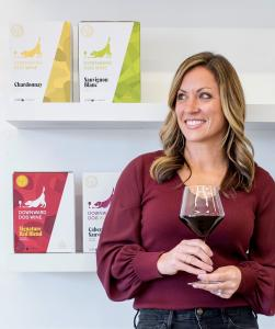 Pretty lady with glass of red wine standing before Downward Dog wine boxes