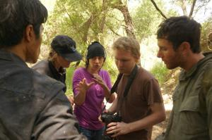 A woman in a purple hat and black beanie holds her hands up as she gives direction to the dark-haired man in a black shirt standing in front of her.  A blonde woman in a black shirt stands to her left looking at the camera being held by the blonde man in