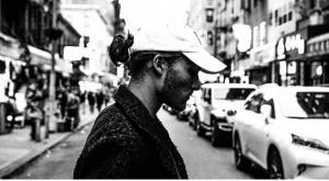 Alex Silver wearing white baseball cap crossing a busy street.
