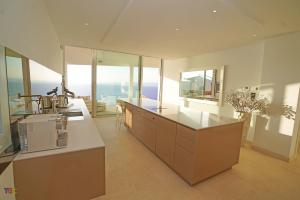 Host indoors in the spacious open living and dining area leading to the designer fully-equipped kitchen.