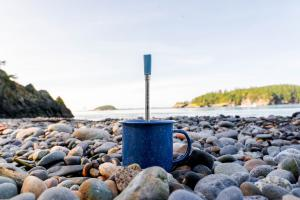 JoGo Straw standing in a blue camping mug, which is sitting on the rocky beach of the Pacific Northwest.