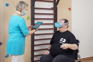 Stroke patient assisted by a therapist using Pico VR headset for stroke therapy with Rehago