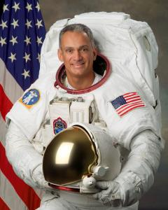 "The official Astronaut portrait of Astronaut John ""Danny"" Olivas in his EVA (aka Spaceswalk) white suit holding his helmet (Photo Credit NASA)"