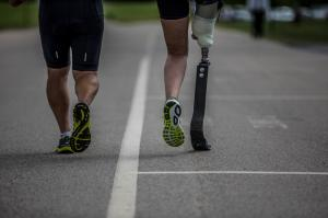 An abled bodied athlete running on the road beside an athlete with a prosthetic running leg