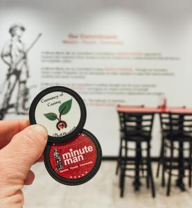 """This picture shows Minute Man's """"Currency of Caring"""" held up in front of the wall of Minute Man Jacksonville, which has the Minute Man Mission displayed for all to read."""