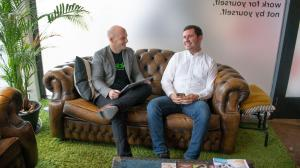 two men from Hable sitting on a sofa, smiling at each other