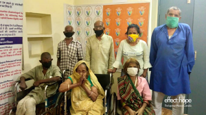 Photo: Two rows of people in India at a vaccine site. Back row from left to right: 2 men wearing black covid masks, a woman wearing a yellow covid mask and a man wearing a green mask. Front row: 3 individuals in wheelchairs. From left to right: one man we
