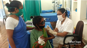A nurse wearing white and a white covid-19 cloth mask inserts a needle into a woman wearing a green sari's arm. The woman receiving the vaccine is affected by leprosy. She wears dark glasses to assist her vision and has a bandage on one hand. A helper (wo