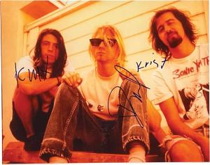 Stunning 14 inch by 11 inch photo of Nirvana sitting together, side-by-side on wooden steps, signed in blue felt tip pen by all three band members.