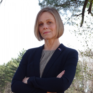 Headshot of Dr. Gillian Battino, a white woman with short blonde hair, wearing a black blazer and American flag pin standing with her arms crossed