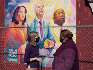 Dr. Gillian Battino, standing talking with Dr. Cherise Easley, a Black woman in front of a painted mural of President Biden, Vice President Harris and the late Congressman John Lewis