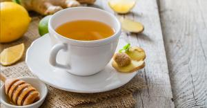 Photograph showing a cup of freshly brewed tea, with a small bowl of honey and slices of fresh ginger, lemon and lime.