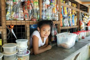 Young female from Phillipine stands content at a counter, showcasing how FundLife protects young girls through non-formal education!