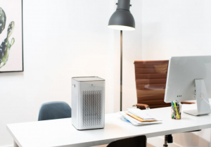 An photograph of a Medify Air purifier sitting next to a computer on a desk in an office.