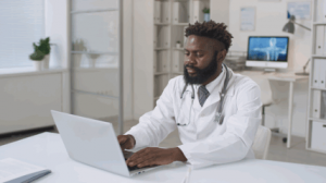 A doctor is typing on a keyboard in a modern medical clinic driven by digital health technology.