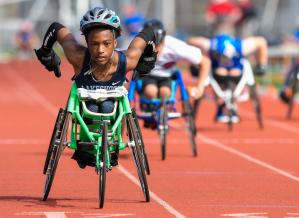 young black athlete competing in wheelchair racing on a track