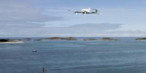 A Skyports delivery drone is shown in flight over the ocean.
