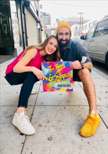 """Anthony & Tiffany Salerno hold the album cover for """"I Am a Worshipper"""" outside FD Studio in Downtown Los Angeles after shooting the music video for their single, """"Stars and Dots,"""" which is the first song on the album."""