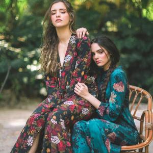 Two beautiful women dreased in long floral dresses reming us o the cottage-core trend.