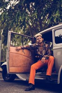 Marshall Hugh sitting in a vintage car facing towards the camera, wearing black boots, orange pants, a 70's style silk shirt, and gold chains.