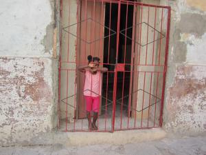 Young girl in Havana standing behind red bars