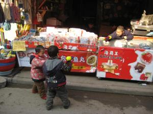 Three boys playing with water guns in Shanghai storefront