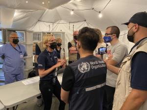 Assessors from the WHO ask International Medical Corps staff members questions during a tour of the EMT Type 1 facility.