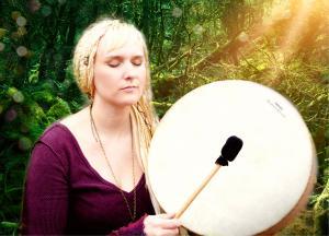 Chakuna plays hand drum, eyes closed, long blond braids and shining light.