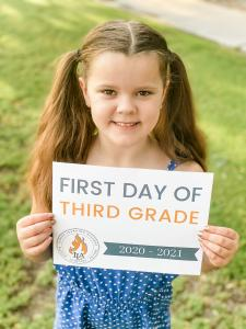 Young girl holding a 'first day of 3rd grade' sign with Ignite Learning Academy's logo.