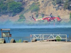 Firefighting helicopter draws water from Iron Gate Lake on the Klamath River to fight the Klamathon Wildfire