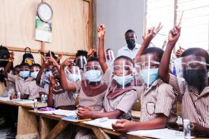 Young students wearing masks and face shields sitting at their desks and raising their hands.