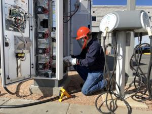 An In-Charge Energy field technician works on an EV charger at a fleet site.