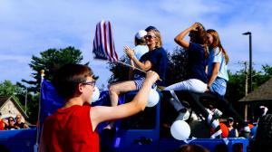 Dr. Battino her family and campaign staff sit atop a blue Jeep Wrangler in a parade precession as it passes by a young boy waiving an American Flag in the foreground