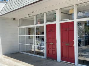 Image shows front of the new gallery at 2323 Central Avenue with red front door and glass front.
