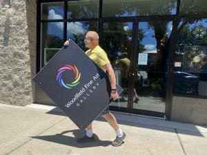 Photo of gallerist and artist Jim Woodfield carrying his logo sign down the street to his new location.