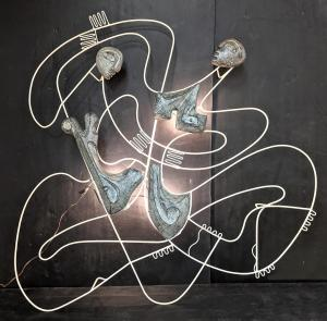 Figural wall sculpture by Frederick Weinberg that lights up, white painted metal armature with molded figures. Estimate: $3,000-$4,000.