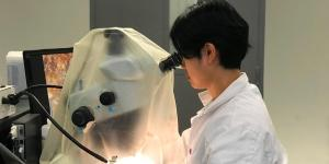An Ocean Wise researchers is using a microscope to undertake forensic microfiber analysis in a laboratory