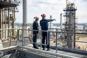 Haldor Topsoe technicians stand on top of a big chemical plant, one of them pointing at a silo installation