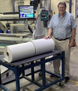 David Gustafson, Marketing Manager For General Data's Coated Products Division, stands with two coated rolls of Jet-Kote™ inkjet print-receptive material at General Data's coating facility in Cincinnati, OH.